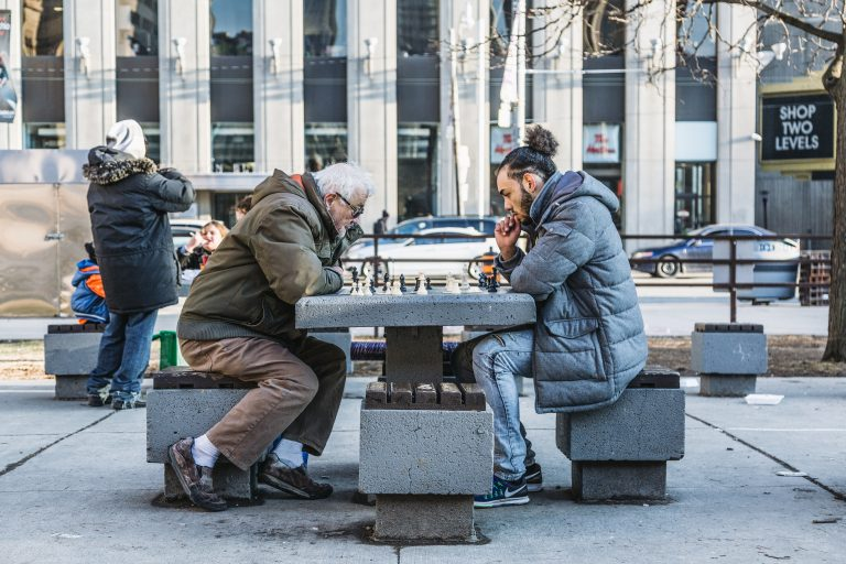 Two people playing chess outdoors